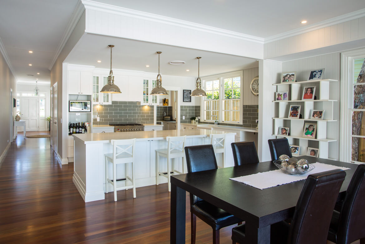 Dining room and kitchen with pendant lights over island bench.